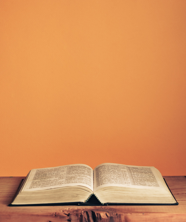 Open Holy Bible on a old wooden table. Beautiful orange wall background.